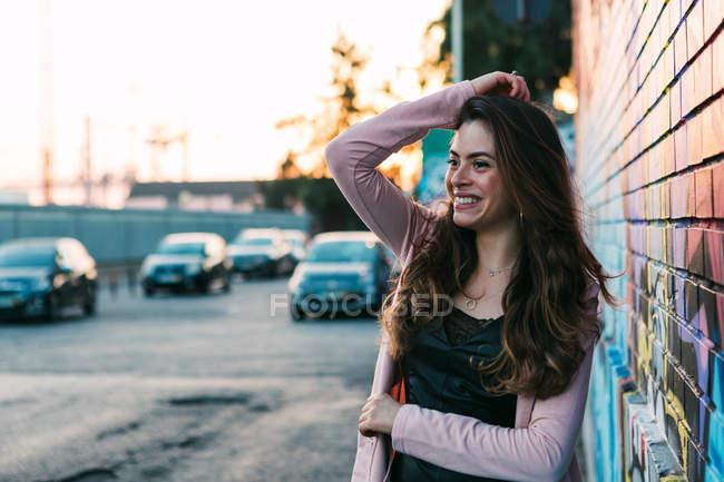 Attraente giovane donna felice con la mano nei capelli in piedi sulla strada — Foto stock