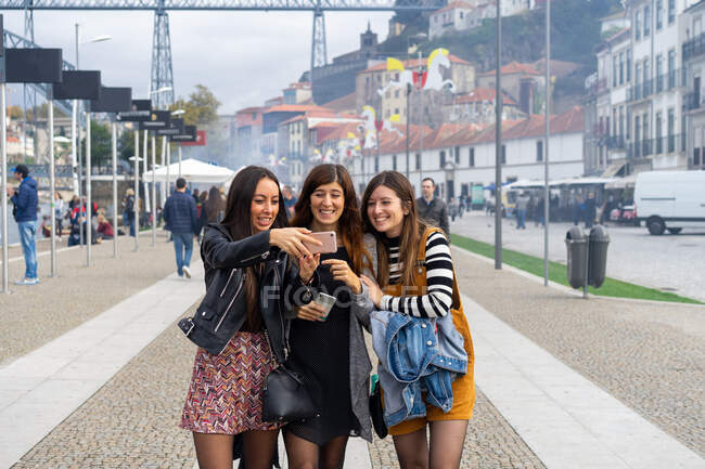 Attractive cheerful ladies taking selfie on mobile phone and walking on footpath near old buildings in Porto, Portugal — Stock Photo