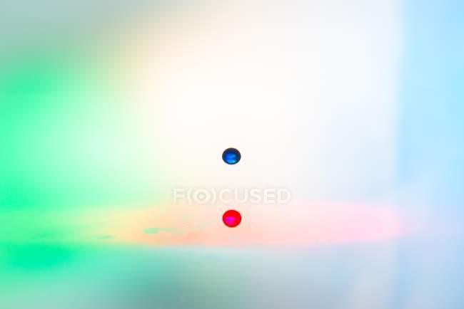 Primo piano colpo di spruzzata di liquido trasparente colorato su sfondo colorato — Foto stock