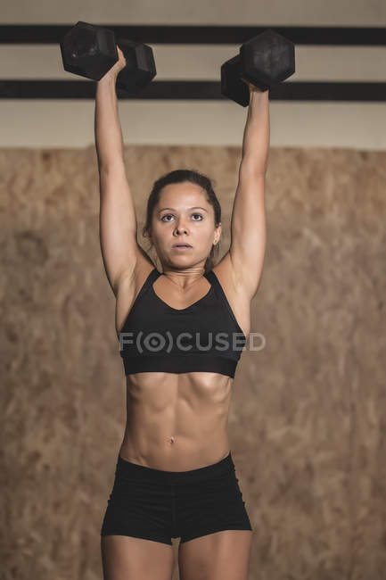 Woman training with dumbbells in sports hall — Photo de stock