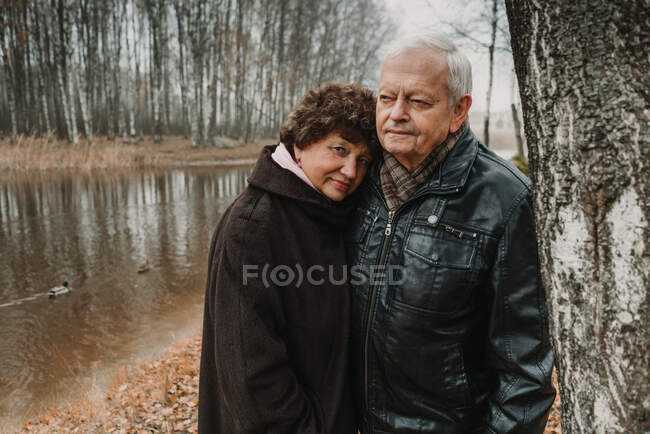 Casal sênior em pé perto do lago — Fotografia de Stock