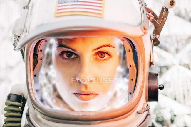 Уверенная в себе девушка в старом космическом шлеме со знаком американского флага на фоне фольги — стоковое фото