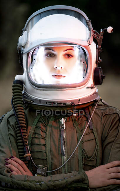 Beautiful woman poses looking at camera dressed as an astronaut. — Stock Photo
