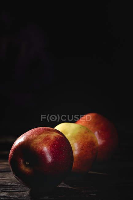 Свежие красные и желтые яблоки на темном фоне — стоковое фото