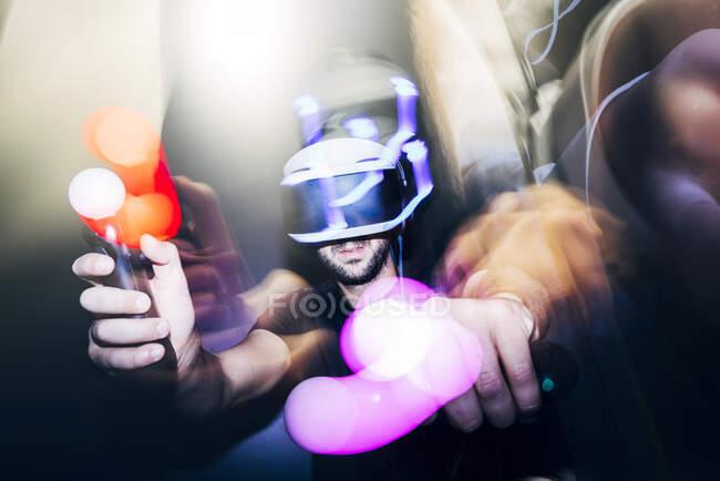 Imagen borrosa y desenfocada del hombre con auriculares VR oscuros y jugando con el controlador - foto de stock