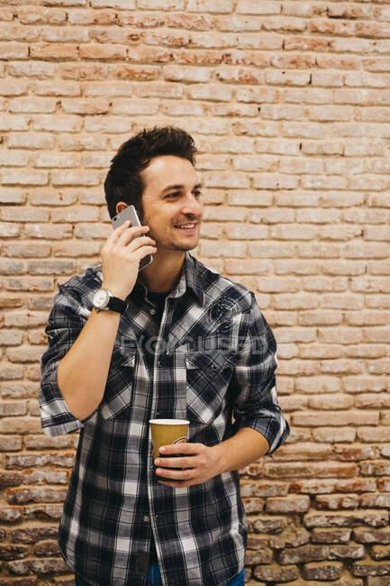Jeune homme avec tasse parlant sur smartphone — Photo de stock