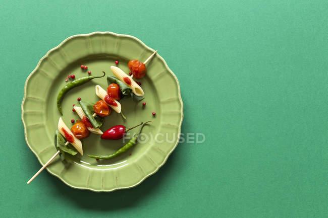 Macarrones con tomate y albahaca sobre palo sobre fondo verde - foto de stock