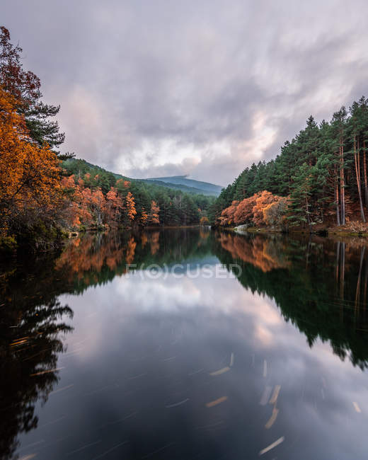 Calm river between autumn forest and hills under cloudy sky — Stock Photo