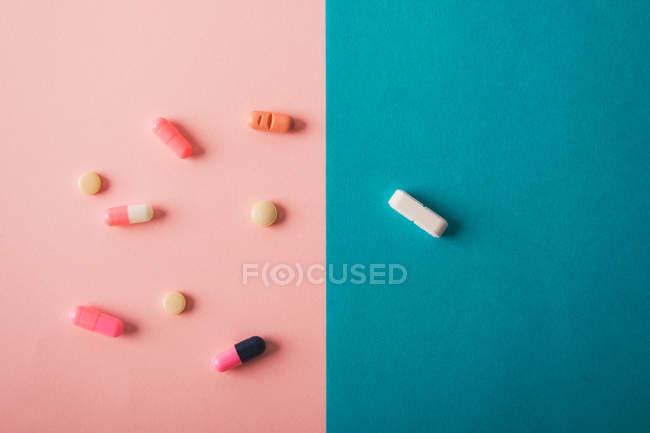 Таблетки и капсулы, разбросанные на голубом и розовом фоне — стоковое фото