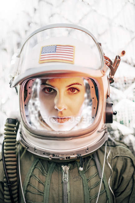 Confident girl wearing old space helmet with american flag sign on foil background — Stock Photo
