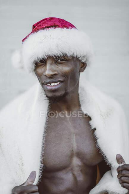 Задоволений чорношкірий чоловік у костюмі Миколая. — стокове фото