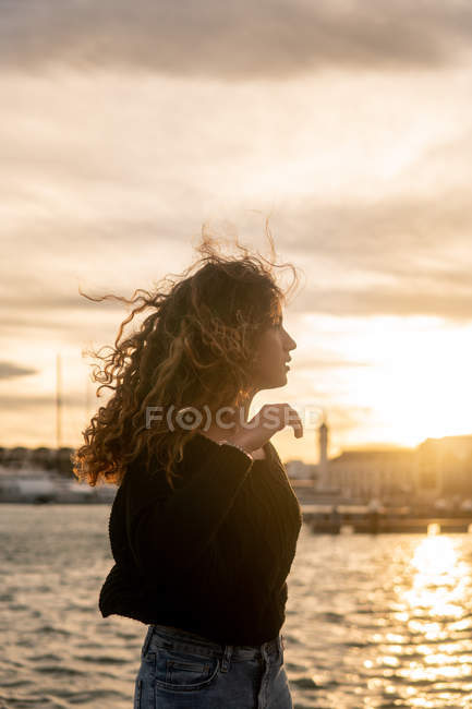 Attractive young lady with curly hair looking away while standing near water during sundown in city — Stock Photo