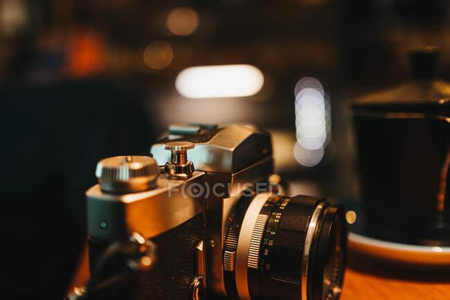 Ретро фотоаппарат лежит на деревянном столе в стильном кафе — стоковое фото