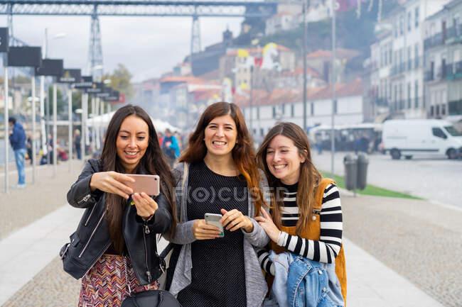 Junge lächelnde Frauen machen Selfie auf dem Gehweg — Stockfoto