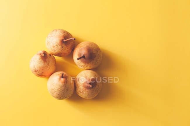 Peras maduras frescas no fundo amarelo — Fotografia de Stock