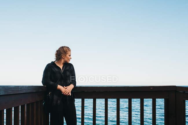 Молодая женщина в повседневной одежде, стоящая рядом с перилами на набережной и любуясь видом на чудесное море в Алтее, Испания — стоковое фото