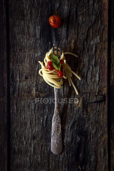 Spaghetti with tomato sauce on fork on dark wooden background — Stock Photo