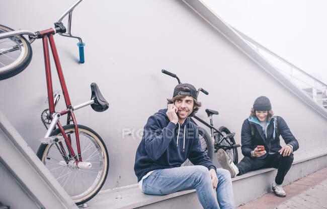 Молоді чоловіки з мобільним і BMX велосипедом.. — стокове фото