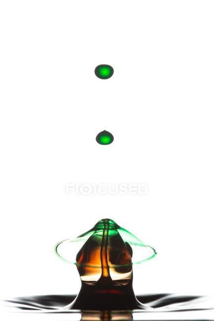 Primer plano de salpicadura de líquido transparente verde sobre fondo blanco - foto de stock