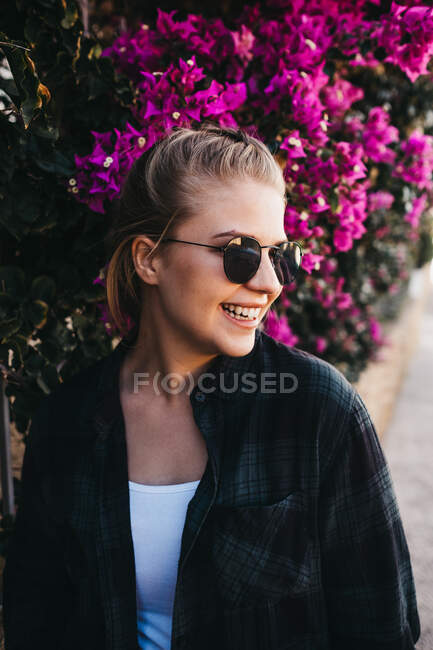 Lovely young lady in trendy outfit and sunglasses looking away while standing near bush with beautiful flowers on street — Stock Photo