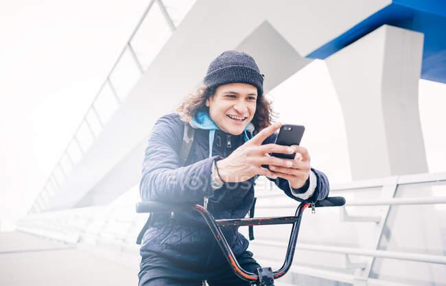 Молодий чоловік позує з мобільним і мотоциклом BMX.. — стокове фото