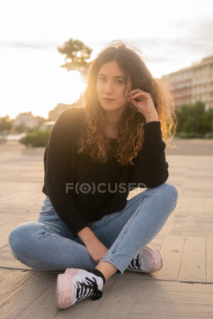 Charming young woman looking at camera while sitting on pavement on city street — Stock Photo