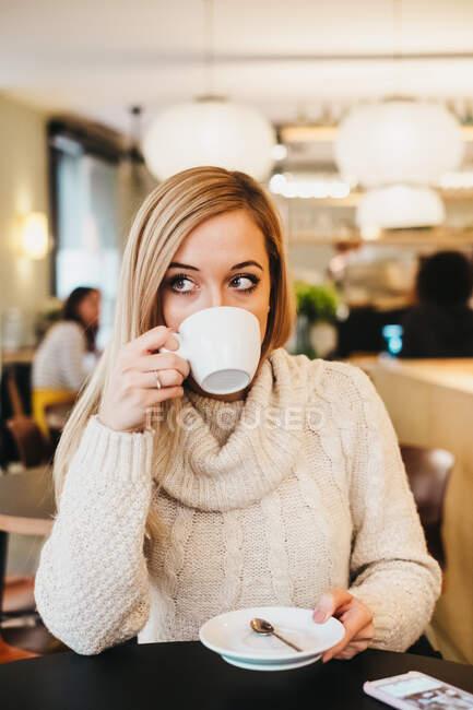 Молода чарівна жінка тримає в кафе чашку. — стокове фото