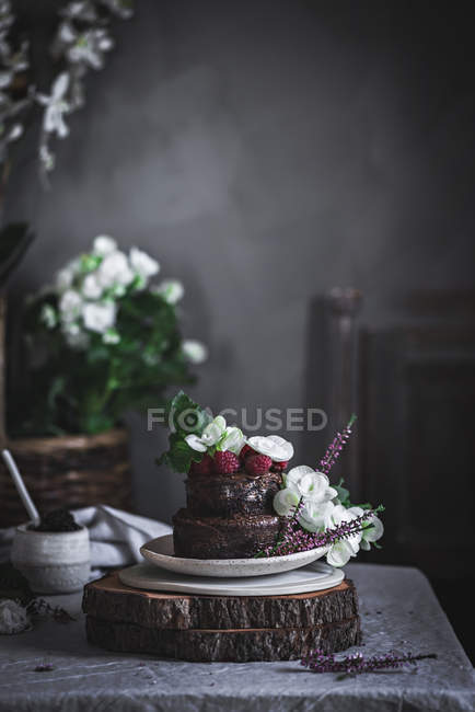 Chocolate cake decorated with raspberries and flowers served on plate on wooden stand — Stock Photo