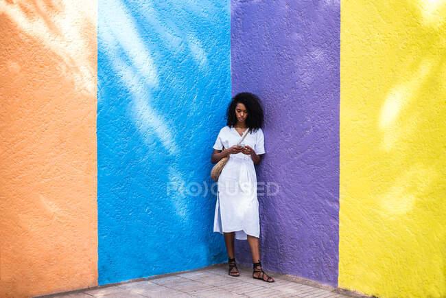 Черная женщина на мобильном телефоне на красочном фоне — стоковое фото