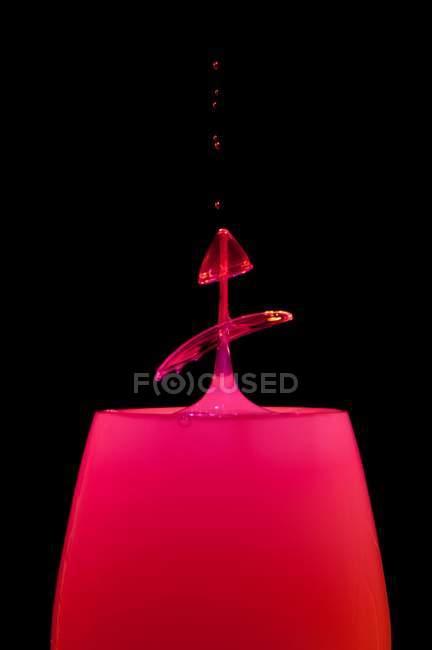 Closeup shot of splash of red liquid on black background — Stock Photo
