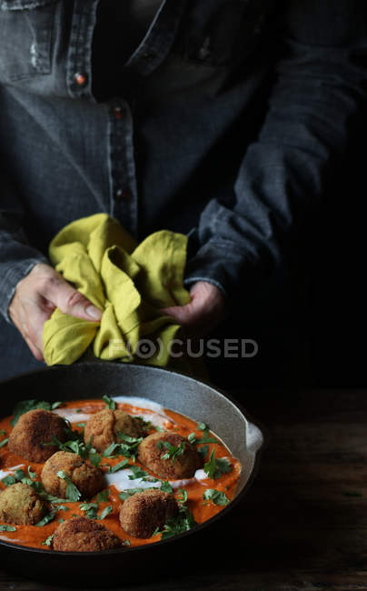 Human hands holding heavy frying pan of yummy cauliflower and quinoa balls with sauce and parsley over wooden table — Stock Photo