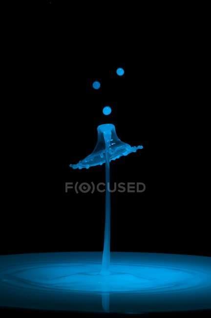 Gros plan de projection de liquide bleu de couleur sur fond noir — Photo de stock