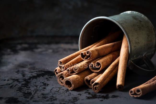Bouquet de bâtonnets de cannelle aromatiques dans une tasse en métal sur une table sombre . — Photo de stock
