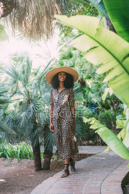 Woman with a straw hat walking in a beautiful garden — Stock Photo