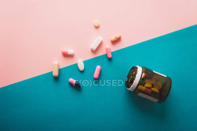 Pillen und Kapseln auf blauem und rosa Hintergrund mit Glas verstreut — Stockfoto