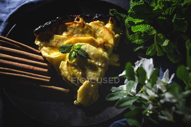 Tarta de manzana con canela y menta servida en plato negro - foto de stock