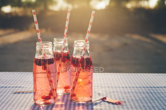 Bottles with fresh fruit drink and drinking straws on table outdoors — Stock Photo
