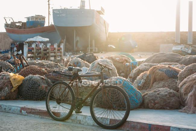 Рыбацкие лодки на якоре с грудами рыболовных сетей в подсветке — стоковое фото