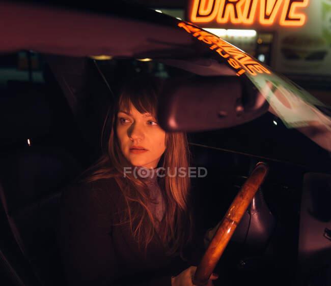 Jeune femme en voiture près du ravitaillement et de la construction avec inscription Kibiniai drive — Photo de stock
