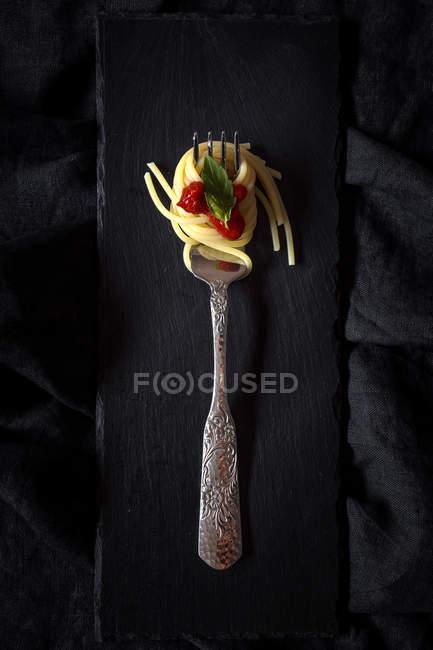 Spaghetti mit Tomatensauce und Basilikum auf Gabel auf Schiefer — Stockfoto