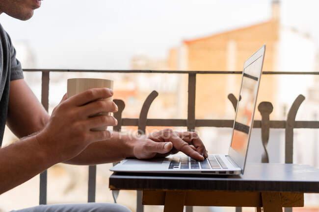 Cultivo hombre con taza de café y el uso de ordenador portátil en el balcón - foto de stock