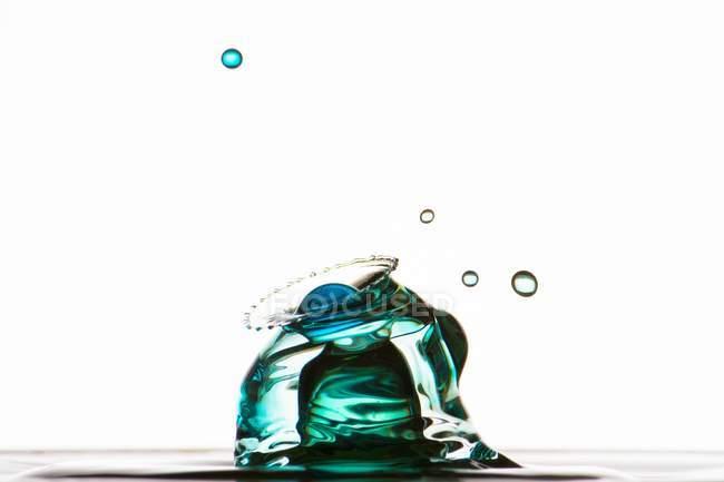 Gros plan de éclaboussures de liquide transparent coloré sur fond blanc — Photo de stock