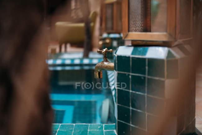 Décor doré du robinet d'eau côté piscine — Photo de stock