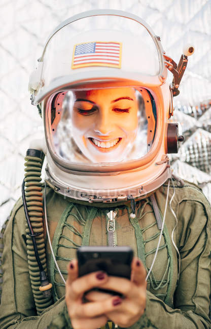 Female astronaut in illuminated vintage helmet with mobile phone — Stock Photo