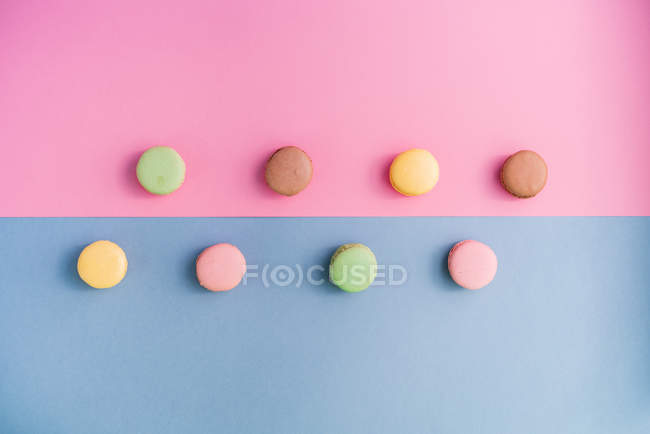 From above collection of bright delicious macarons on pink and blue background — Stock Photo