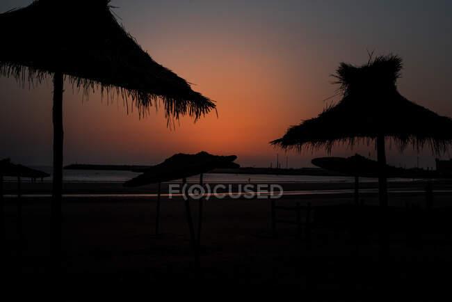 Beach sunset and straw umbrella — Stock Photo