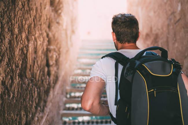 Homme montant les escaliers à travers les murs d'argile à Marrakech, Maroc — Photo de stock
