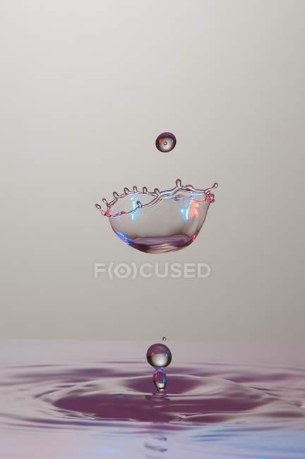 Крупный план брызг прозрачной жидкости цвета на сером фоне — стоковое фото