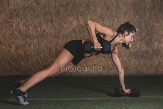 Вид сбоку на женщину в спортивном костюме, которая занимается гантелями и поднимает вес в спортзале — стоковое фото
