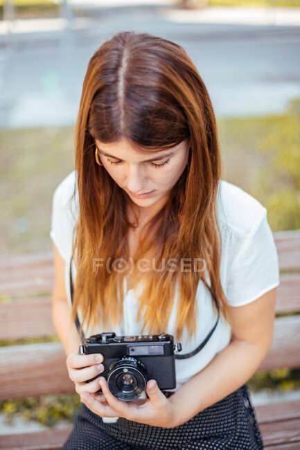 Giovane ragazza in posa con una fotocamera vintage — Foto stock